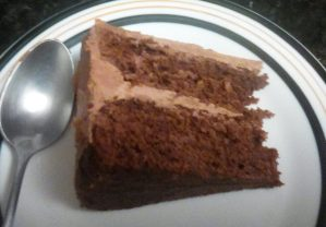 A slice of chocolate cake with chocolate buttercream frosting